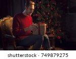 man wraps a christmas gift | Shutterstock . vector #749879275