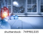 Small photo of white wooden table with space for your product ad or promotional text. White big open window, snowflakes falling. Winter night view of the mountains and the great moon.