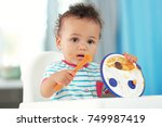 cute baby with spoon and plate... | Shutterstock . vector #749987419