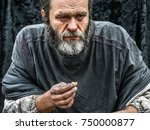 Small photo of poor man homeless with dirty hands eating piece of bread in modern capitalism society