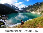 Hiker on the Blanca Lake, Washington. State. Located in the Henry M. Jackson Wilderness Area, Beautiful turquoise green lake. Only accessible by foot. Elevation Gain: 2700 ft in. 5 hours, 8 miles. - stock photo