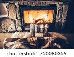 feet in woollen socks by the... | Shutterstock . vector #750080359
