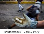 Small photo of CARACAS, VENEZUELA - MAY 01, 2017: Protest in Caracas, Venezuela against the government of Nicolas Maduro. Protester shows a cartridge shot of buckshot.