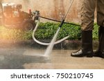 worker cleaning driveway with... | Shutterstock . vector #750210745