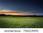 bundles of hay on the meadow by ...   Shutterstock . vector #750219091