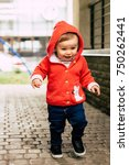 Small photo of Funny adorable baby girl in red knitted hoodie and jeans walking in the city