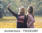 two young girls in park taking... | Shutterstock . vector #750281089