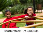 siblings playing on roundabout | Shutterstock . vector #750330331