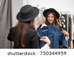 gorgeous young woman trying on... | Shutterstock . vector #750344959