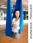 Small photo of Young modern woman with gadget sitting in swing in gym and practicing aero yoga