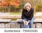 elderly lady grabbing her knee... | Shutterstock . vector #750423181