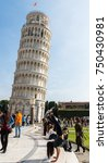 Small photo of Pisa, Italy - October 28th, 2017: Young tourist does a somersault in front of Leaning Tower of Pisa while someone snaps her picture