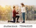 Small photo of Marry me. Horizontal shot of young man in casual clothing standing on one knee and holding engagement ring while making wedding proposal to his beautiful girlfriend. Engagement of young couple.