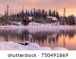 Snowy Cabins Line The Shore Of...