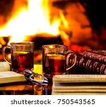 Small photo of Two glass mugs of hot drink or alcoholic drink or mulled red wine and antique books in front of warm fireplace. Magical relaxed cozy atmosphere near fire. Autumn or winter concept