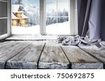 Small photo of Wooden table with free space for your product or promotional text. Open window with snowfall. Landscape of winter forest mountains and small dock at the end of the village.