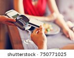 Small photo of Picture showing people paying in restaurant by credit card reader