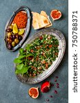 Small photo of Middle Eastern traditional dinner. Authentic arab cuisine. Meze party food. Tabbouleh, muhammara, olives. Top view, flat lay, overhead