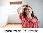 girl measuring height standing... | Shutterstock . vector #750796309