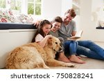 Stock photo father reading book with son and daughter and pet dog at home 750828241