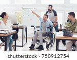 Small photo of A colleague rolls a person in a wheelchair around the office. They have fun and laugh. They are spending their time in bright office.