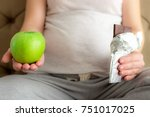 a pregnant woman holding a... | Shutterstock . vector #751017025