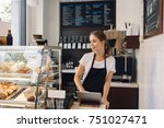 Stock photo portrait of young caucasian female woman cashier seller using touch pad for accepting client 751027471