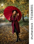 Small photo of Beautiful girl in claret coat and black hat standing near colorful autumn leaves with umbrella. Art work of romantic woman .Pretty tenderness model under rain looking afar.