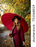 Small photo of Beautiful girl in claret coat and black hat standing near colorful autumn leaves with umbrella. Art work of romantic woman .Pretty tenderness model under rain looking down.