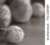 Small photo of A small ball of woolen yarns closeup on a background of wool yarn. Balls of white wool yarn for knitting.