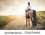 girl riding her horse in a path ... | Shutterstock . vector #751474441