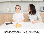 Small photo of Mother scolds her son while he listening music and doesn't listen. Copcept of family conflict