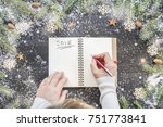 Woman Hands Writting Xmas Wishlist Goals Resolutions on Empty Blank Letter Notebook to Santa Claus on Black Wooden Table with Christmas Festive Decoration Fir Branches Snow Flat Lay Top View