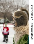Small photo of Profile of referee in ram makeup and disguise with young goalie in front of hockey net in soft focus background during the Montreal Snow Festival, Jean-Drapeau Park, Montreal, Quebec, January 24, 2016