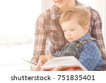 mother reading book for her son.... | Shutterstock . vector #751835401