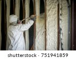 Small photo of Worker spraying closed cell spray foam insulation on a home that was flooded by Hurricane Harvey