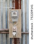 Small photo of Temporary house kilowatt hour meter link with power cutter by cable on the wooden board on the alumium sheet wall in the construction site.