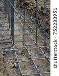 Small photo of Construction site view of supported grid of steel rebar reinforcement, vertical aspect