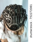 Small photo of patterns on the head of a thin braid in a girl, a hairdress of a sphinx, spirals of braids, abstract drawings of hair, creative shaving