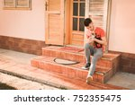young man holding a little dog... | Shutterstock . vector #752355475