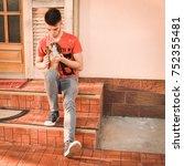 young man holding a little dog... | Shutterstock . vector #752355481