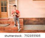 young man holding a little dog... | Shutterstock . vector #752355505