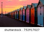 Small photo of a line of 30 beach huts with a diminishing perspective, the nearer beachhuts are big, lamp post and promenade, brighton seafront
