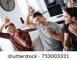 men are putting on birthday hat.... | Shutterstock . vector #753003331