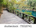 Wooden road in the forest park near the lake - stock photo
