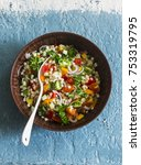 Small photo of Israeli cous cous ptitim vegetables tabbouleh salad on a blue background, top view. Vegetarian food concept