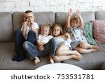Small photo of Big family of four cheerful excited children sitting on comfortable sofa in living room, playing words guessing game. Happy emotional Caucasian siblings fooling around at home on big grey couch