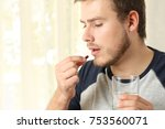 serious man taking a pill... | Shutterstock . vector #753560071