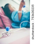 Small photo of Closeup of hand adjust iv hose for patient. Illness asian child admitted at hospital room. Girl lying on sickbed with saline intravenous (IV) drip on hand. Health care stories. Vintage film effect.