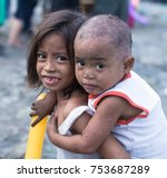 Small photo of Manila, Philippines - Nov 21 , 2014: Poor girl with emotional smile trying to be brave though adversary. Taking care of her little brother. Life in the philippine slum.